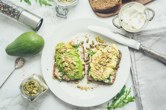 Toasts d'avocat sains pour le petit déjeuner ou le déjeuner avec du pain de seigle, du fromage à la crème, de la roquette, des tranches d'avocat, des courges, du chanvre et des graines de sésame, du sel et du poivre. Concept de nourriture végétarienne Mangez propre. Vue supérieure.