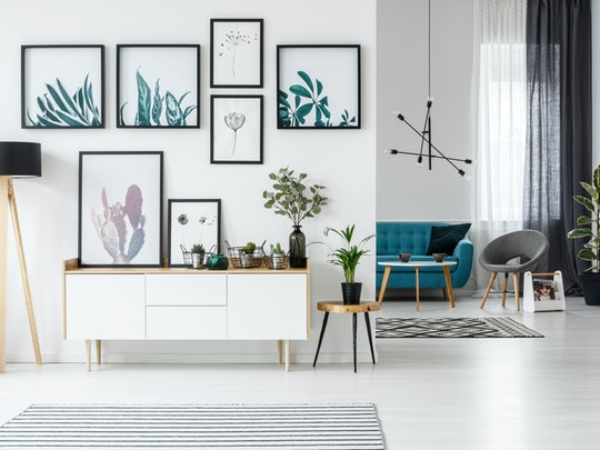 White living room interior with botanical posters on the wall and sofa in the background