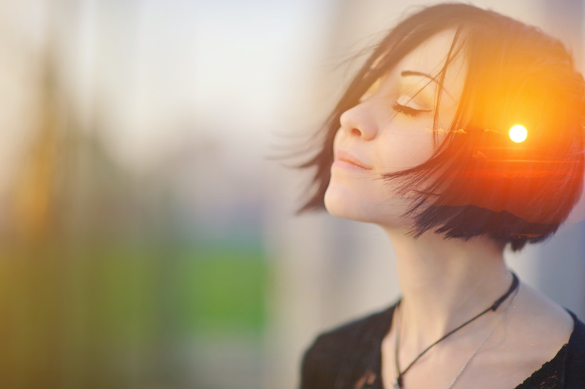 Double multiply exposure portrait of a dreamy cute woman meditating outdoors with eyes closed, combi...