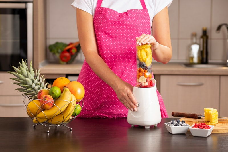 Detail of female hands holding a blender bowl filled with fresh fruit for making a smoothie; woman wearing apron standing next to a kitchen counter and making smoothie in a blender