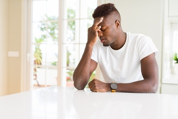 Handsome african american man on white table at home tired rubbing nose and eyes feeling fatigue and headache. Stress and frustration concept.