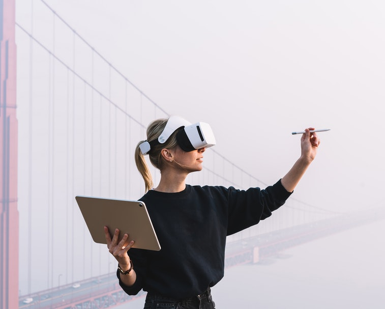 Young female extend hand with digital pencil for interactive touch over air while standing in against bridge construction wearing virtual reality headset. Hipster girl designing pen copy space with VR