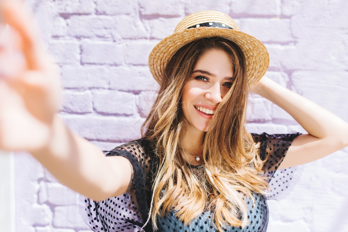 Close-up portrait of happy girl with mid-back length hair making selfie and holding straw hat. Outdo...