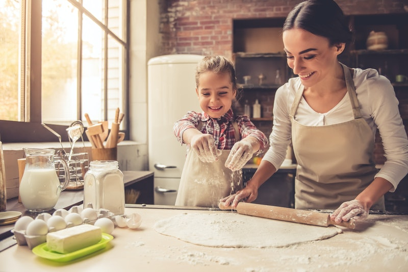 Cute little girl and her beautiful mother are flattening the dough using a rolling pin and smiling while baking