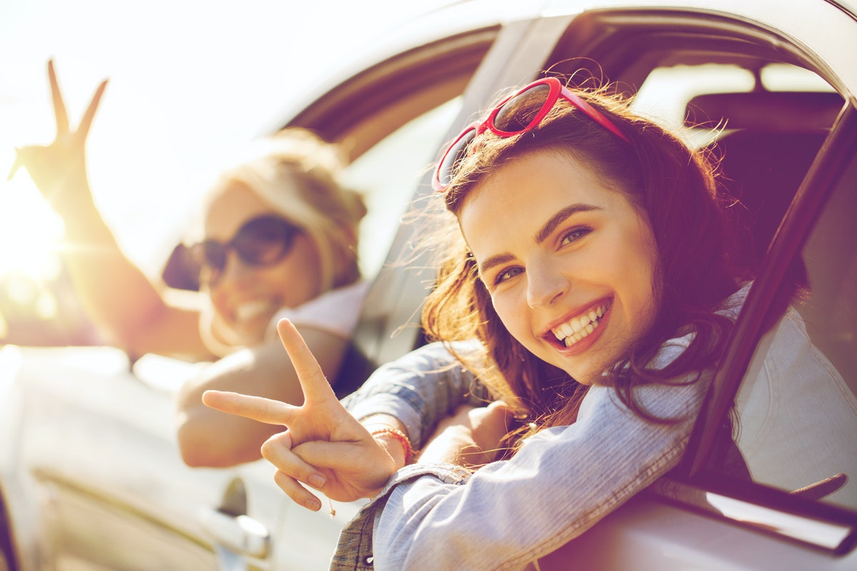 summer vacation, holidays, travel, road trip and people concept - happy teenage girls or young women...