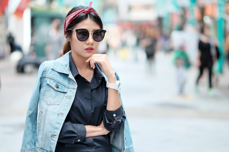 Asian girl wearing blue jean jacket, sun glasses and red headband walking on street with blurred background, asian girl street fashion portrait