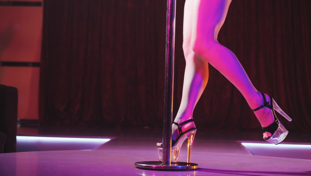 Young sexy slim woman pole dancing striptease with pylon in night club. Beautiful naked stripper girl on stage