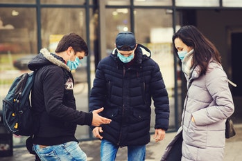 Global pandemic. Coronavirus disease. People in a medical mask outdoors. Coronavirus epidemic. Non-contact greeting. Coronavirus prevention. Foot shake style of greetings.