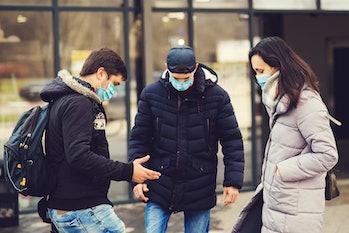 Global pandemic. Coronavirus disease. People in a medical mask outdoors. Coronavirus epidemic. Non-contact greeting. Coronavirus prevention. Foot shake style of greetings.