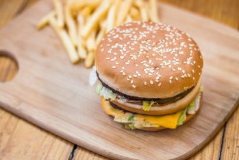 Fast food set big hamburger and french fries on wood background