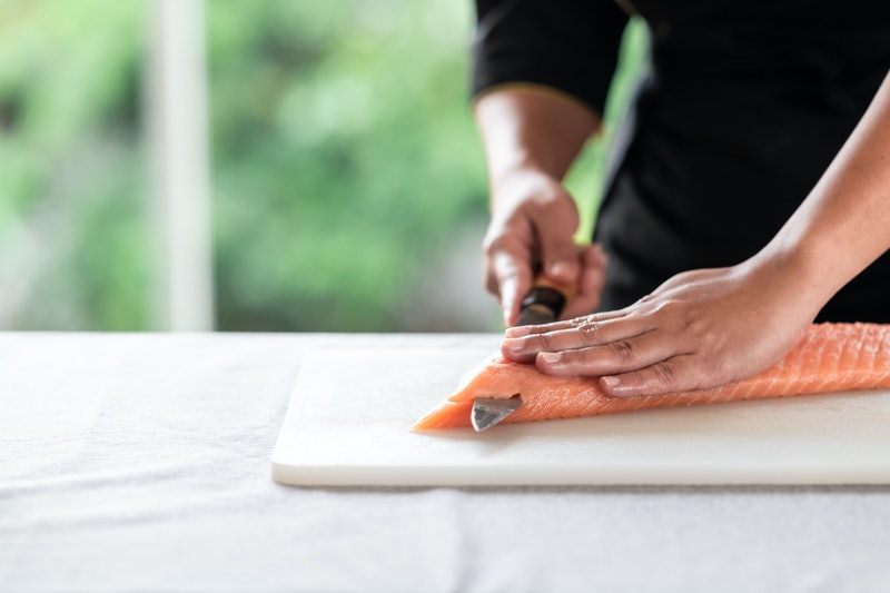 Chef slicing raw salmon on plastic plate. Asian woman chef in black uniform, start to slice.