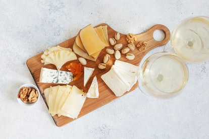 Cheese plate served with white wine, crackers and nuts, Top view. Assorted cheeses Camembert, Brie, Parmesan blue cheese, goat
