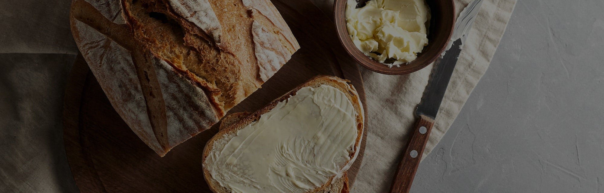 Artisan sliced toast bread with butter and sugar on wooden cutting board. Simple breakfast on grey c...