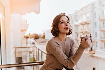 Dreamy dark-eyed girl drinking tea at balcony. Photo of caucasian well-dressed female model holding ...