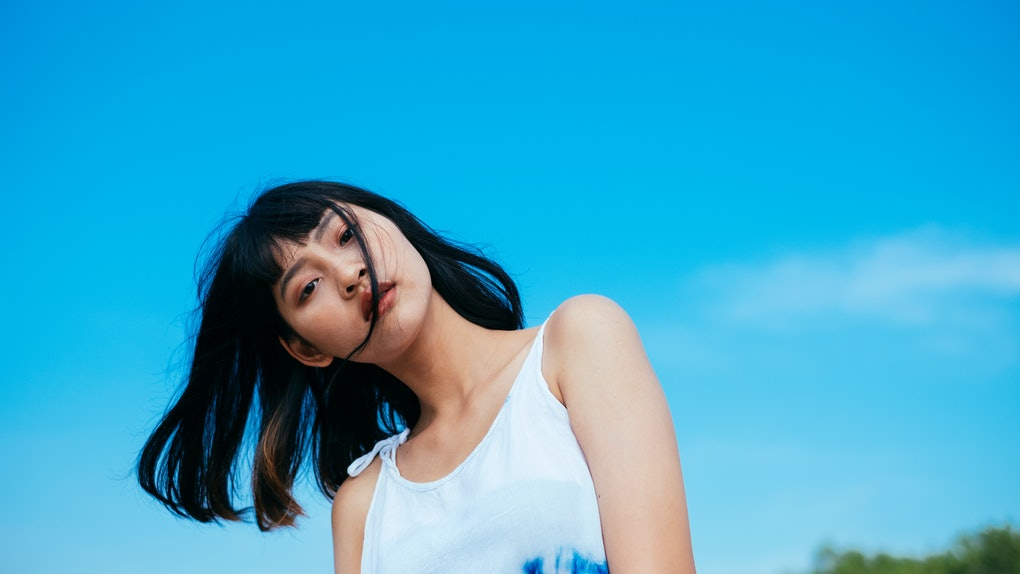 A young woman poses in a tie-dye tank top against a bright blue sky.