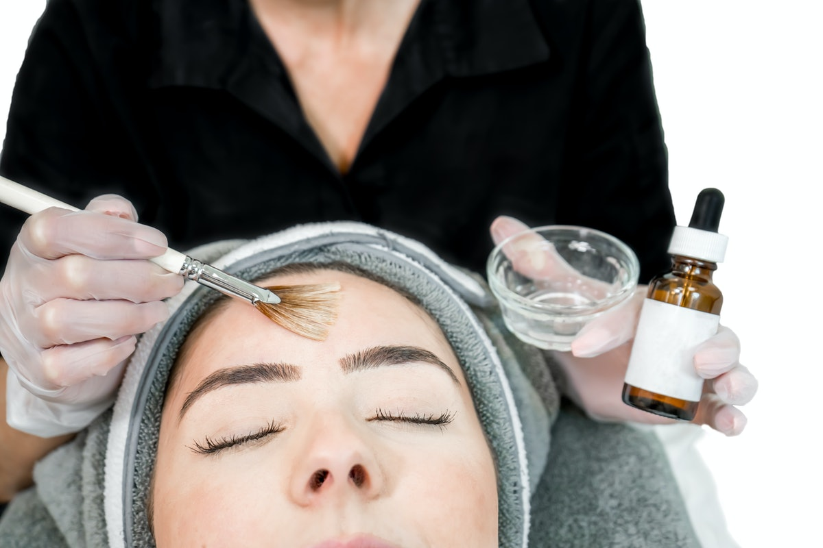 Close up of beautician (cosmetologist) applying chemical peel treatment on patient in a beauty spa, ...