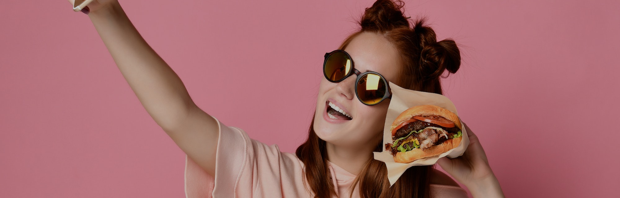 Positive ginger young woman pose for selfie, use modern cell phone, sit with burger in hand , have funny expressions, share photos in social networks, connected to wireless internet.