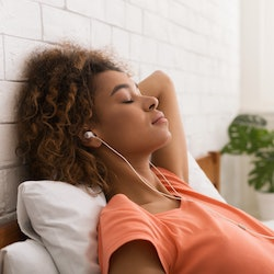 African-american woman relaxing and listening to music, lying in bed in the morning