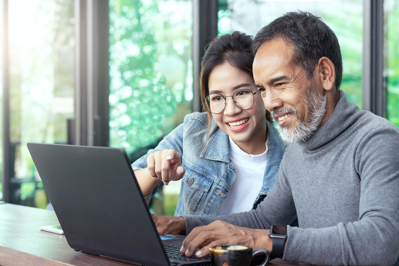 Attractive mature asian man with white stylish short beard looking at laptop computer with teenage eye glasses hipster woman in cafe. Teaching internet online or wifi technology in older man concept.