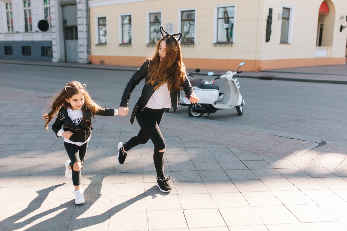 A young woman wearing black jeans, a leather jacket, and cat ears smiles and runs on a sidewalk while holding her niece's hand.