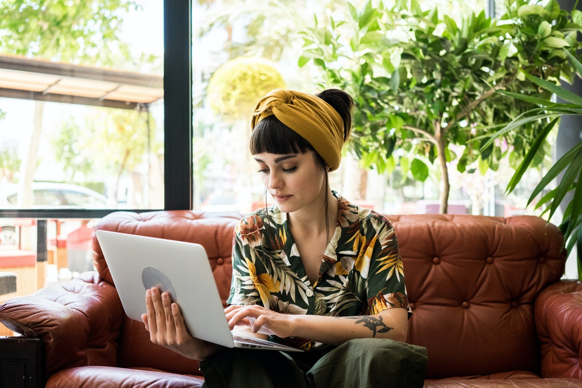 Pretty brunette girl checks her mail on small portable laptop while waiting her order in cafe shop. ...