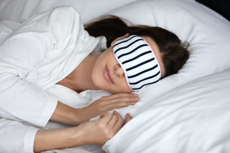 Calm serene young woman wear pajamas and sleeping mask resting in comfortable white bed, peaceful healthy beautiful lady lying asleep on soft pillow orthopedic mattress enjoying good sleep concept