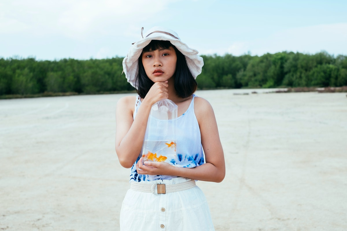 A young woman stands on the beach in a tie-dye shirt with a bag of goldfish in her hands.