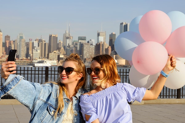 Two happy friends take a selfie, while holding balloons with the New York City skyline in the background.