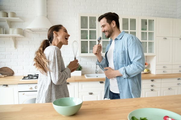 A young couple laughs and sings in their bright kitchen while getting ready to make breakfast.