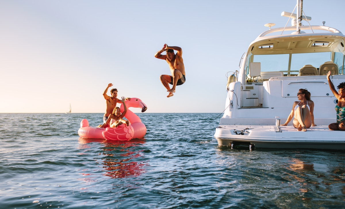 A group of friends relax on a boat and jump into the water at sunset.