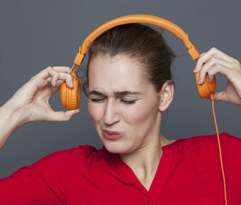 tinnitus headphones concept - stressed out 20s girl listening to loud music with earphones on,removi...
