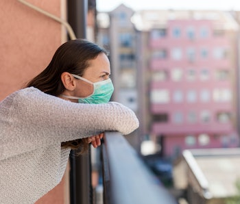Portrait of young woman in home isolation standing on a balcony, wearing surgical mask outdoors as part of coronavirus protection and prevention protocols