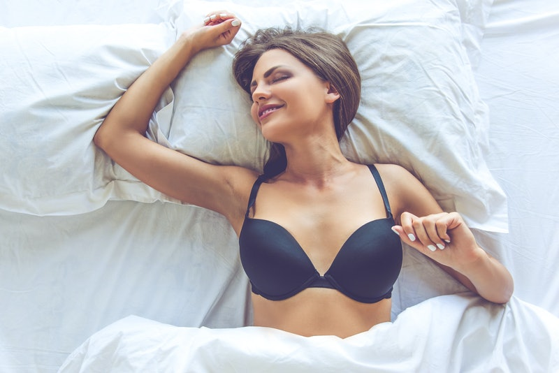 Top view of beautiful sexy young woman in black bra stretching herself and smiling while lying in the bed