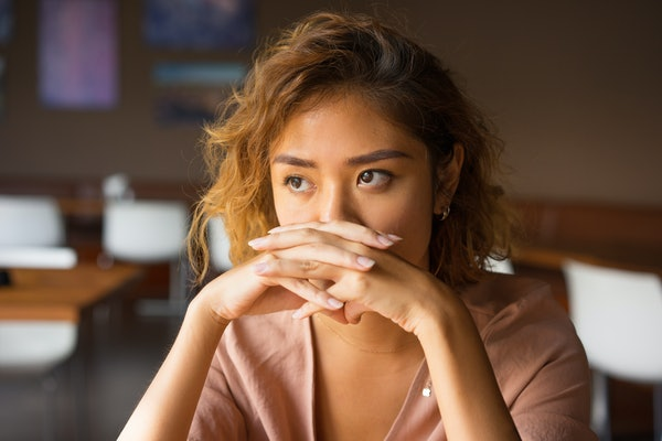 Serious Woman Covering Mouth with Clasped Hands