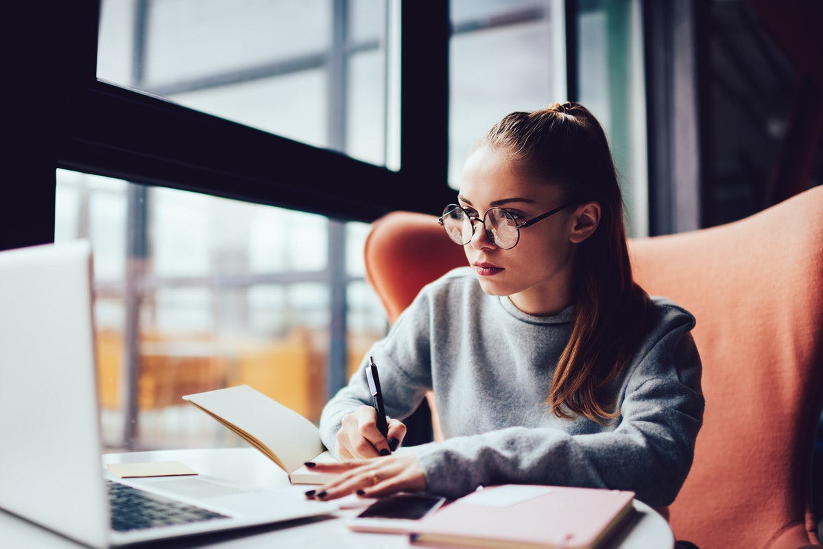 Pensive young student in spectacles making notes in copybook while watching webinar on laptop and learning new information.Skilled copywriter analyzing content of web site making plan of work