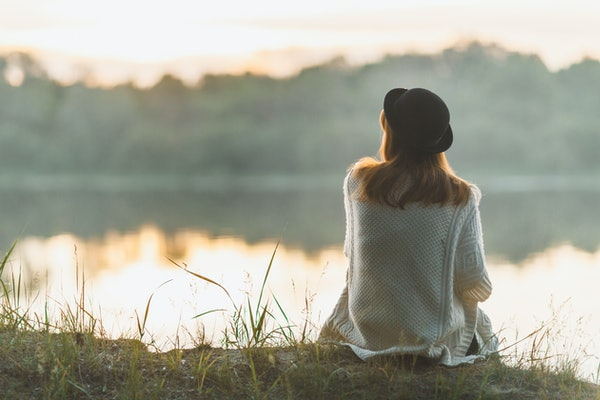 A girl sitting on the river bank in silence