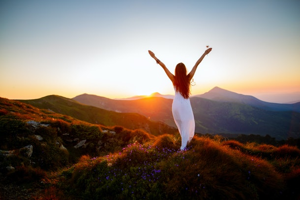 Hiker woman standing with hands up achieving the top. Girl welcomes a sun. Conceptual design. Successful woman hiker open arms on sunrise mountain top. Girl in long white dress in the mountains.