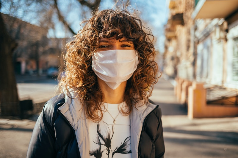 Happy young woman wearing facial mask for virus protection standing outdoors on sunny spring day.