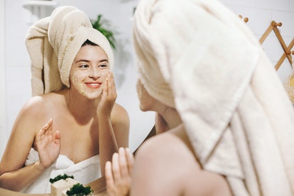 Skin Care concept. Young happy woman in towel making facial massage with organic face scrub and look...