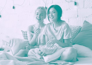 A couple eats popcorn in bed, while watching a movie together.
