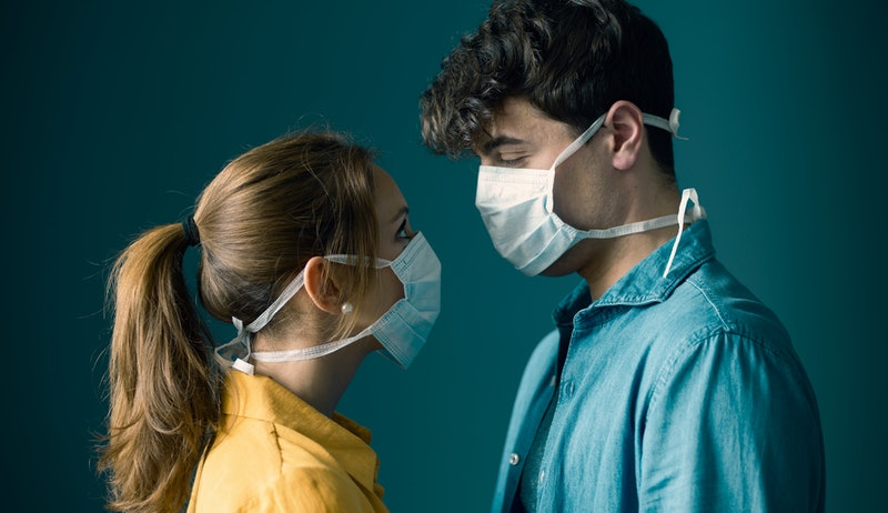 Young romantic loving couple wearing a protective face mask and staring at each other's eyes, pandemic and feelings concept