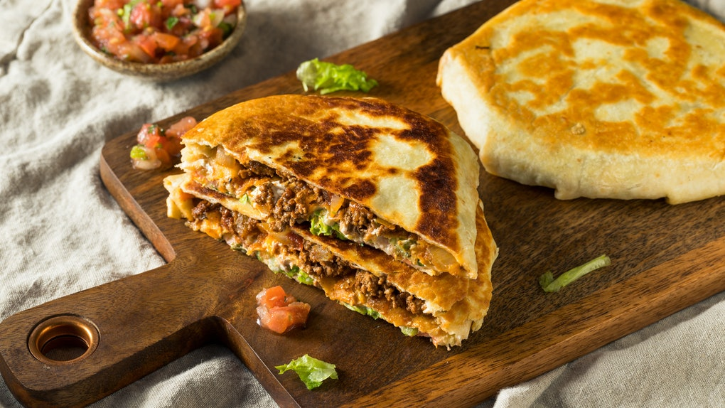 A homemade beef Crunchwrap Supreme like at Taco Bell, sits on a cutting board with lettuce and tomatoes.