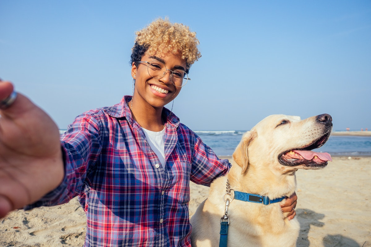 A happy woman hugs her dog on a tropical beach, while snapping a selfie.