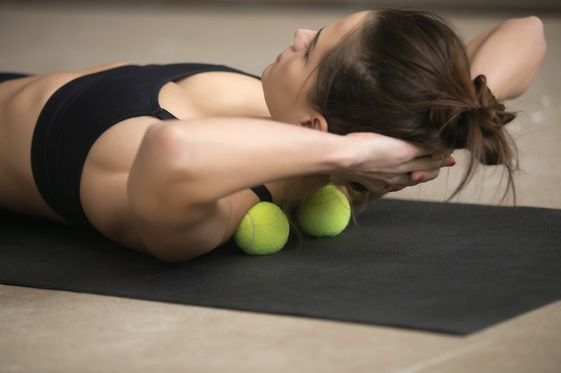 Lifestyle shot of young attractive female practicing self-massage technique applying tennis balls for neck and shoulder pain relief, working out on fitness mat on grey studio floor background, closeup