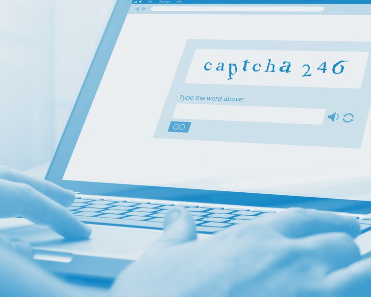 man using a laptop with captcha on the screen. Screen graphics are made up.