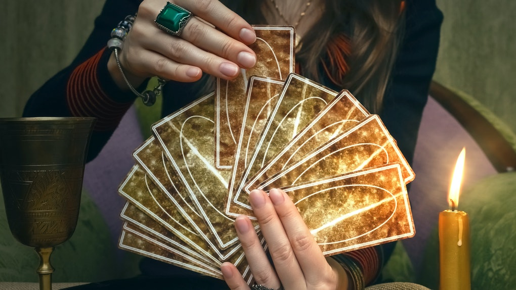 Tarot cards on fortune teller desk table. Future reading. Woman fortune teller holding and hands a deck of tarot cards and shuffles it.