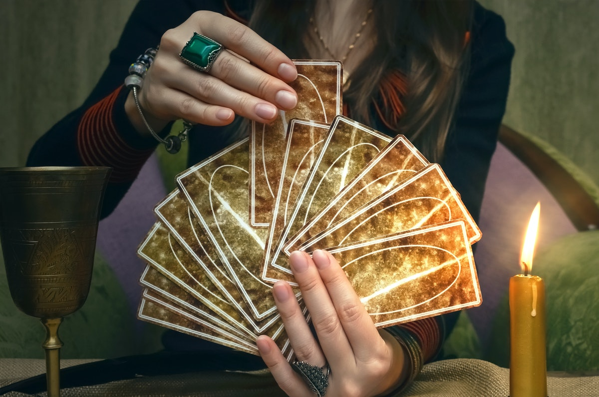 Tarot cards on fortune teller desk table. Future reading. Woman fortune teller holding and hands a d...
