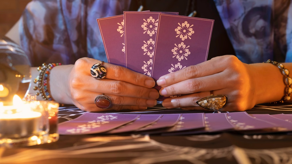 Tarot reader or Fortune teller of hands holding up purple deck tarot cards.Tarot cards spread on table near burning candles and crystal ball.Forecasting concept.