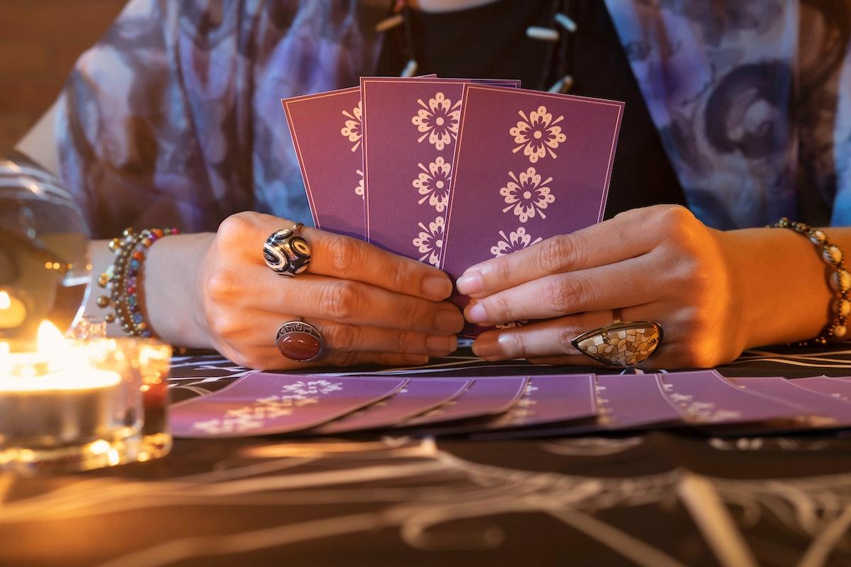 Tarot reader or Fortune teller of hands holding up purple deck tarot cards.Tarot cards spread on tab...
