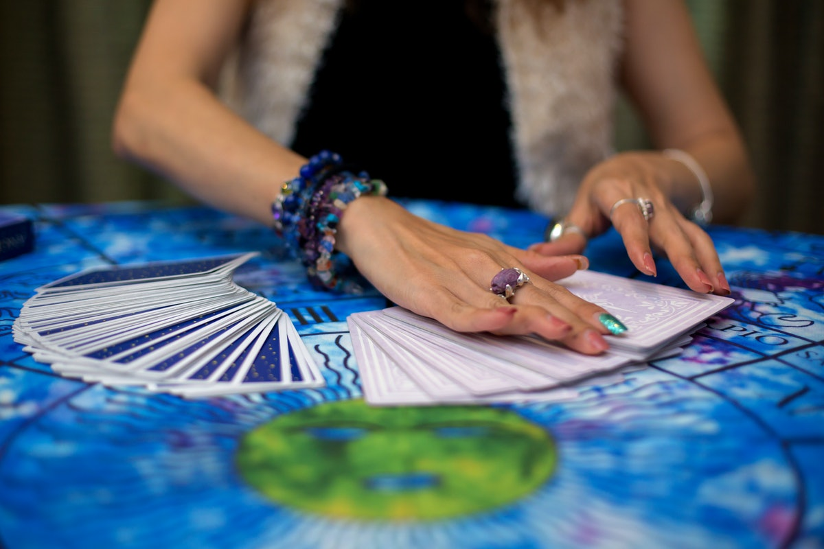 The fortune teller is using cards and crystal glass balls to see the fortune on the horoscope table...